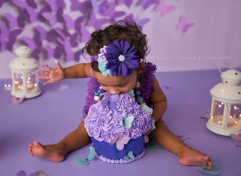 Children Photography Session - Purple Butterfly themed First birthday of a little girl biting into her cake by Gypsy's Corner Photography-1Web