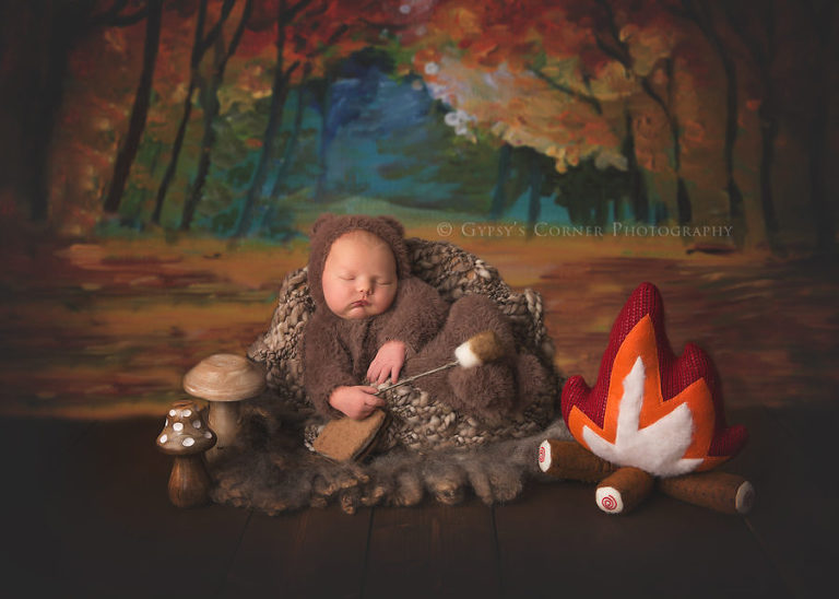 Best Buffalo Baby Photographer - Newborn boy dressed as a bear roasting marshmallows and making smores by Gypsy's Corner Photography in Buffalo NY